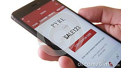 Buscar un código de la cupón para un descuento en el smartphone almacen de video