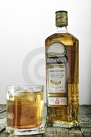 Bushmills whiskey glass and bottle on green wooden table Editorial Photo