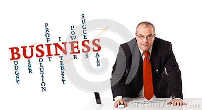 Businesman sitting at desk with business word cloud