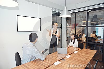 Business blonde woman presenting a project on blank screen TV Stock Photo