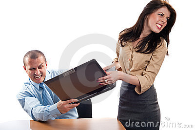 Business colleagues fighting for a laptop