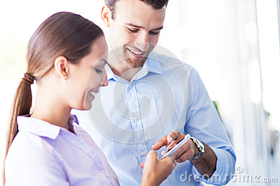 Business colleagues looking at mobile phone