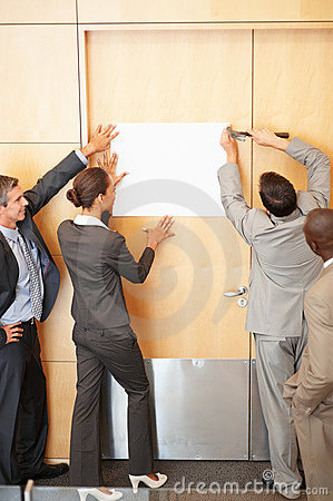 Business colleagues putting up a paper on door