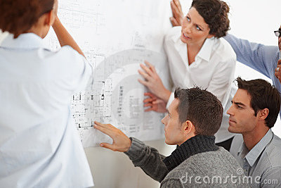 Business colleagues studying a chart on the wall