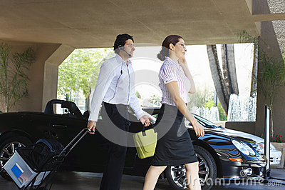 Business Couple Passing By Car