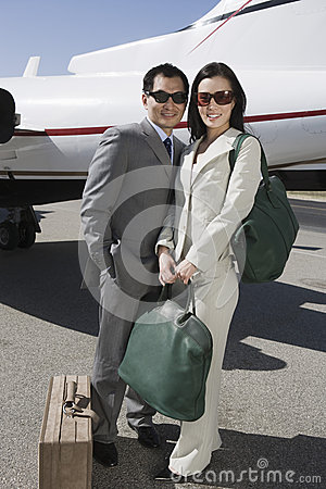 Business Couple Standing Together At Airfield