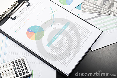 Business and financial report with pen and calculator on wooden