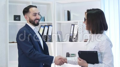 Business handshake - two businesspeople shaking hands to conclude deal or agreement.  stock footage