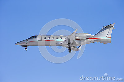 Business jet taking off isolated on a blue sky background.