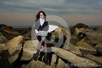 Business lady sitting on the rocks by the sea, aga