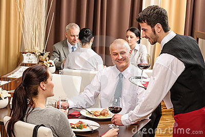 Business lunch waiter serving red wine