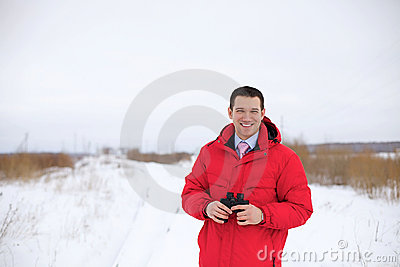 Business man with binocular in winter field