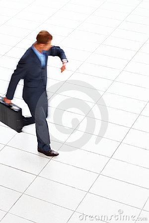 Business man carrying briefcase  checking the time