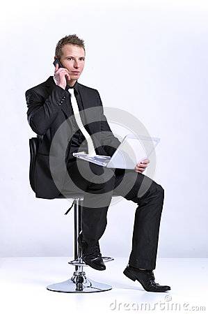 Business man on cell phone in front of laptop