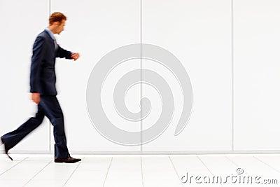 Business man checking time walking fast