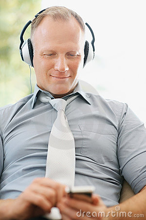 Business man enjoying music on an mp3 player