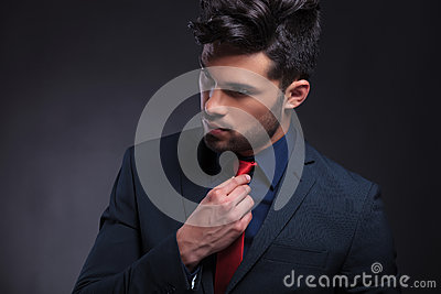Business man fixing his tie and looking away