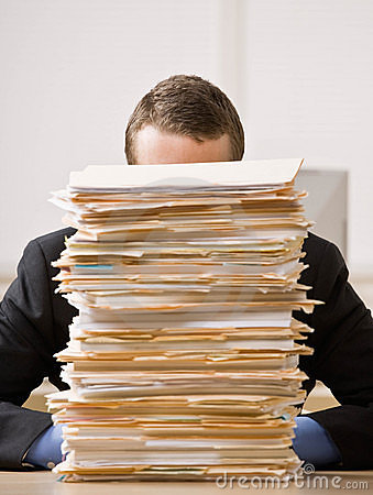 Business man hiding behind tall stack of folders