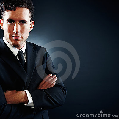 Business man with his hands folded on a dark