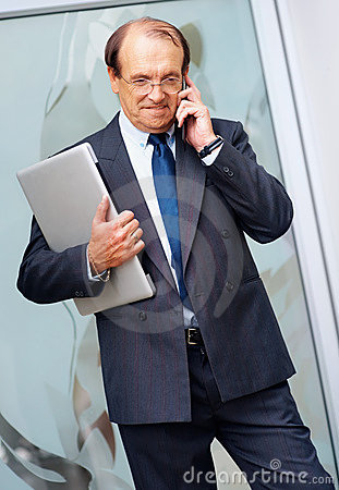 Business man holding laptop while on the phone