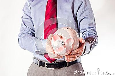 Business man holding a pig bank