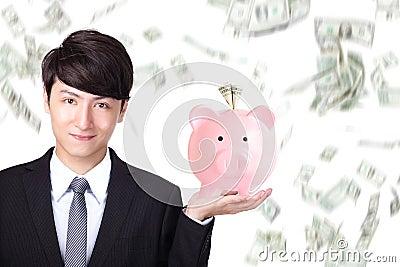 Business man holding pink piggy bank