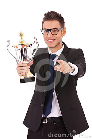 Business man holding a trophy and pointing