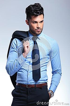 Business man holds jacket on shoulder