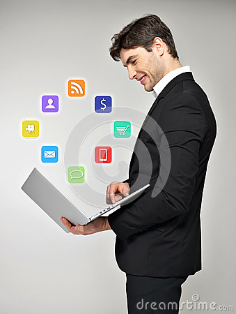 Business man with laptop in hand and media icon
