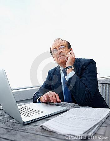 Business man with a laptop on phone looking up