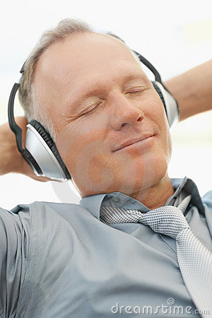 Business man listening to music on an mp3 player