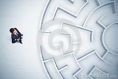 Business man looking at circular maze with nowhere to go