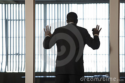 A Business man looking out through a glass wall in