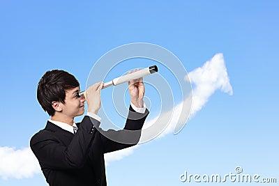 Business man looks through a telescope