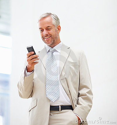 Business man messaging using a mobile phone