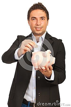 Business man put coin to piggy