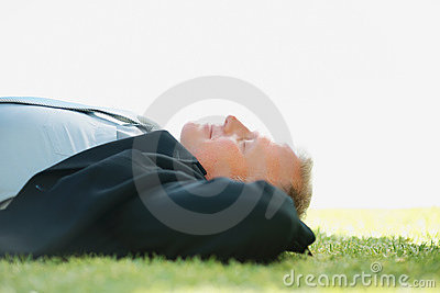 Business man relaxing on the grass