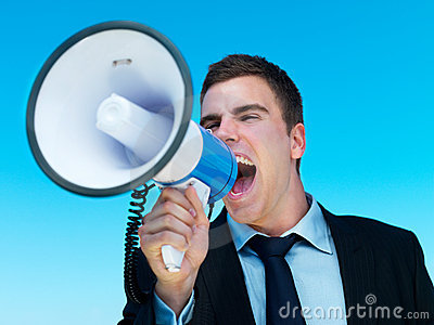 Business man shouting into megaphone