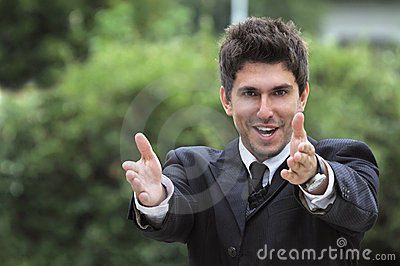 Business man in a suite, pointing at camera to y