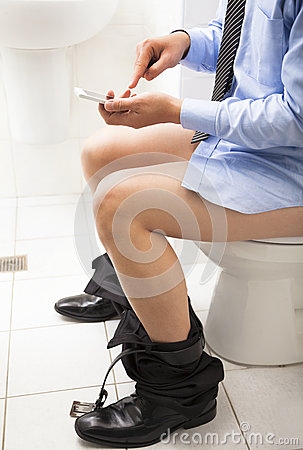 Business man in toilet using smart phone