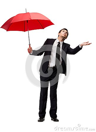 Business man with umbrella checks the rain