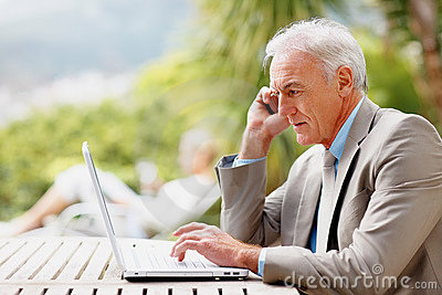 Business man using a laptop and cellphone outdoors