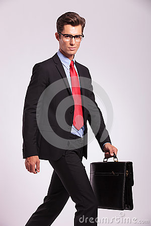 Business man walking & looking at you