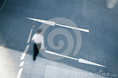 Business man walking with two arrows