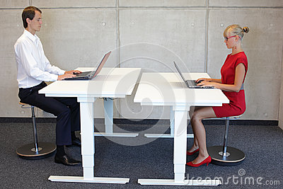 Business man and woman in correct sitting positions in office Stock Photo