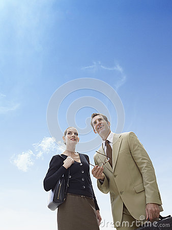 Business man and woman standing against blue sky