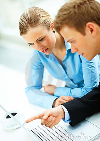 Business man and woman using laptop in a meeting