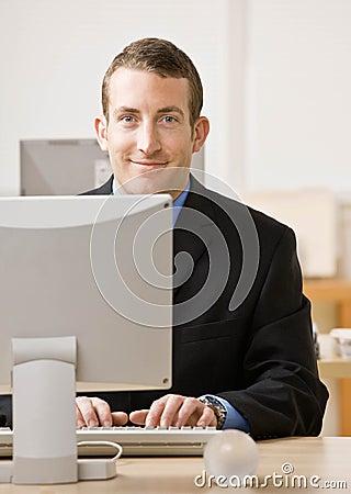 Business man works on desk top computer