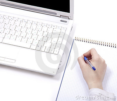 Business notebook with laptop and pen in hand.