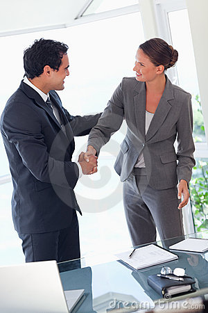 Business partner shaking hands after closing a deal